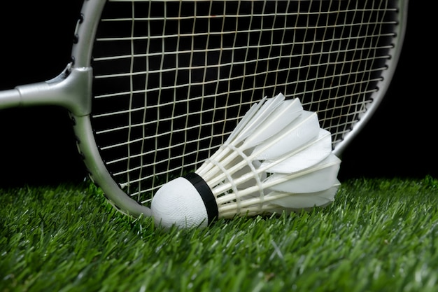 Badminton shuttlecock on grass with racket