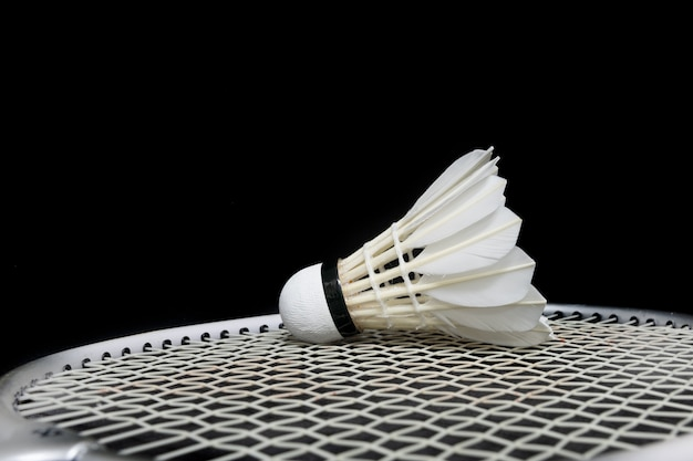 Badminton shuttlecock and racket on grass and black background