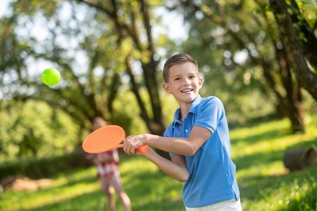 Бадминтон, лето. счастливый милый мальчик начальной школы играет в бадминтон в зеленом парке в солнечный день
