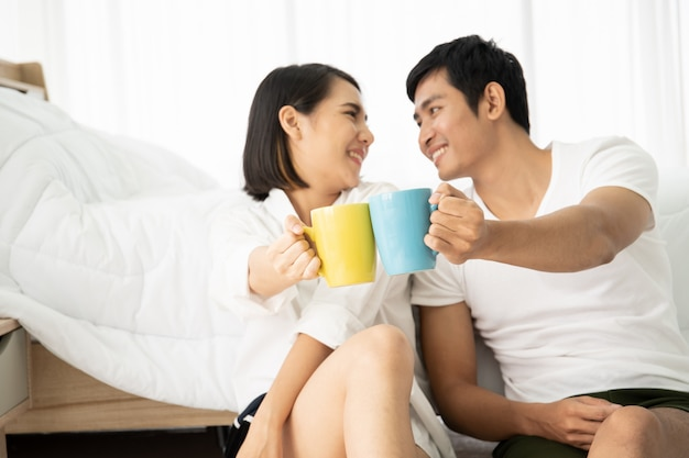 Азиатские молодые пары наслаждаясь вместе с кофе в утре в badroom, отдыхе, паре, отношениях и валентинке. фотография с copyspace.