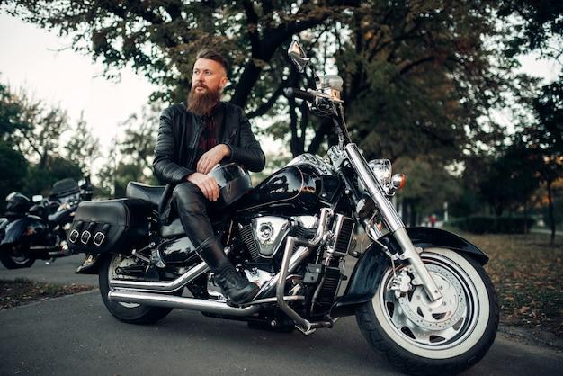 Baerded biker poses on chopper leaning on a helmet