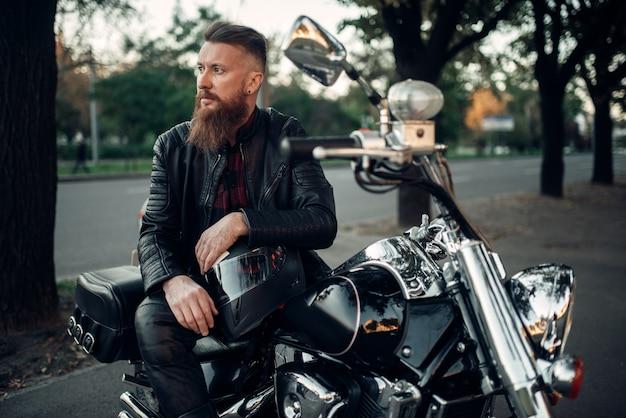 ヘルメットに寄りかかってチョッパーにポーズをとるバイカー。ヴィンテージバイク、ライダーと彼のバイク、自由なライフスタイル、サイクリング
