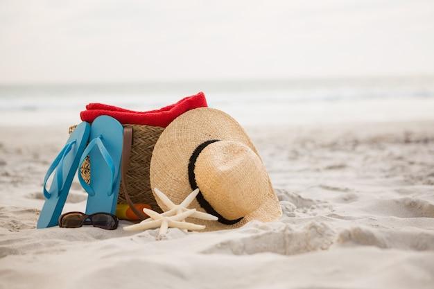 모래 위에 보관 된 가방 및 비치 액세서리