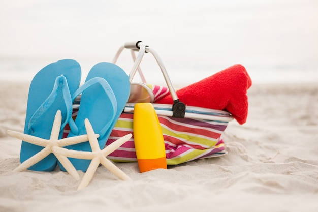 Bag and beach accessories kept on sand