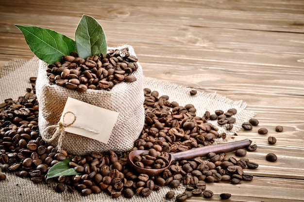 Bag of burlap filled with coffee beans on wooden background.