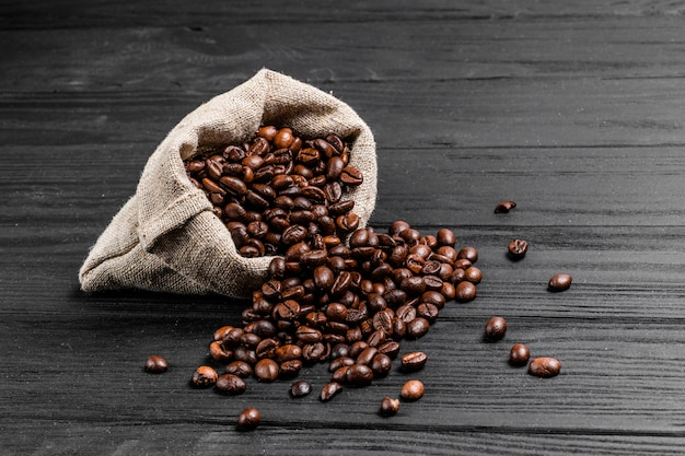 Bag of coffee beans and some scattered seeds on the wood