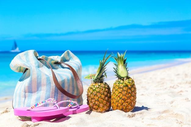 Сумка, шлепанцы, коктейли из тропических ананасов пина колада на пляже карибского моря