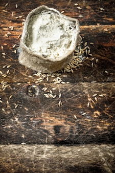 Bag of flour of wheat on a wooden background