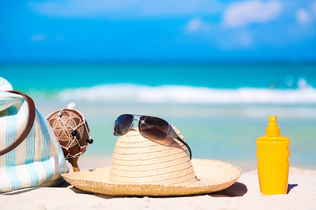 Bag, maracas, straw hat with sunglasses and sunscreen lotion bottle on white sand