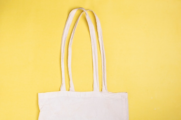 Bag mockup cotton canvas. eco textile bag on yellow paper, top view