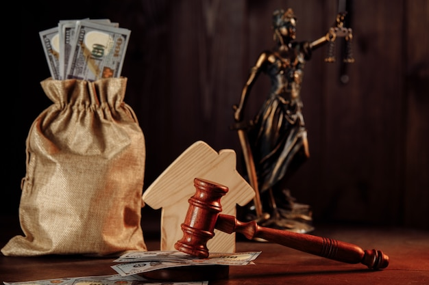 Bag of money house and gavel with lady of justice real estate auction concept