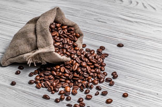 천연 갈색 커피 원두와 흩어져있는 씨앗은 가벼운 나무입니다. 볶은 커피 곡물이 테이블에 자루를 쏟아져 나옵니다.