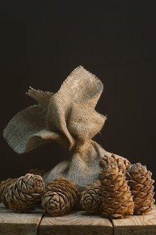 A bag of natural matting on a wooden stall surrounded by cedar cones