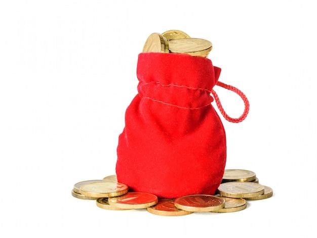 화이트 절연 동전과 밝은 빨간색 직물의 가방. 현금 절약의 개념.