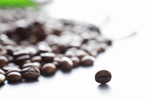 コーヒーの袋。テーブルの上で焙煎したコーヒー豆。料理用の緑の葉とコーヒー豆。