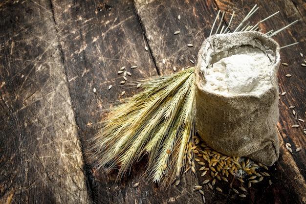 木製の背景に小麦粉と小麦の小穂の袋