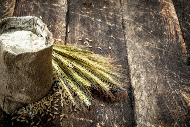 Мешок муки и колоски пшеницы на деревянном фоне