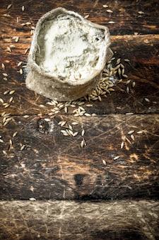 Мешок пшеничной муки на деревянном фоне