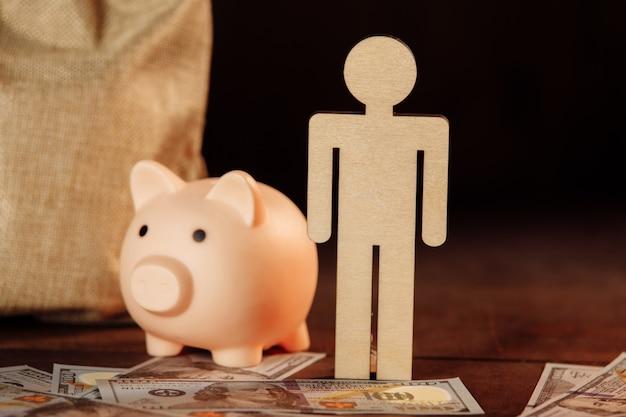 お金の貯金箱の袋と男のクローズアップの図投資と貯蓄の概念