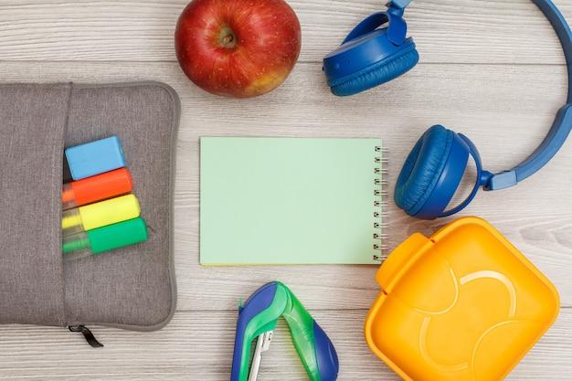 Сумка-пенал с цветными фломастерами и маркером, яблоко, блокнот, степлер, наушники и ланч-бокс на сером деревянном фоне. вид сверху с копией пространства. снова в школу концепции. школьные принадлежности.
