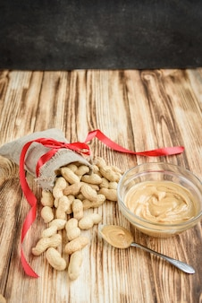 The bag of raw peanuts in shell, glass bowl of peanut butter on wooden background with copy space. flatlay. heathy food.