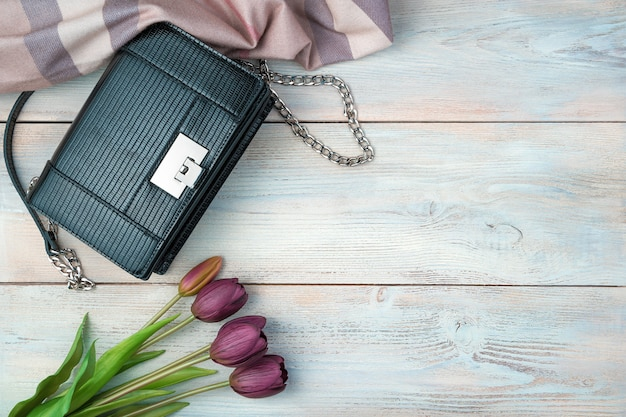 Bag, scarf and flowers on a light wooden background. top view with space to copy.