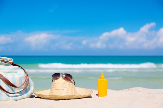 Bag, straw hat with sunglasses and sunscreen lotion bottle on tropical sand
