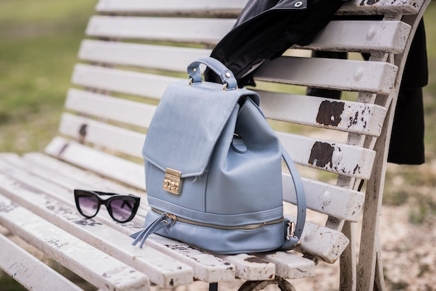 Bag and sunglasses on a bench outdoors