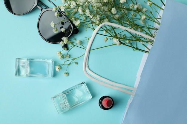 Bag, sunglasses, perfumes, lipstick and flowers on blue background