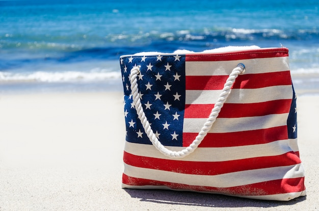 Bag with american flag colors near ocean on the sandy beach