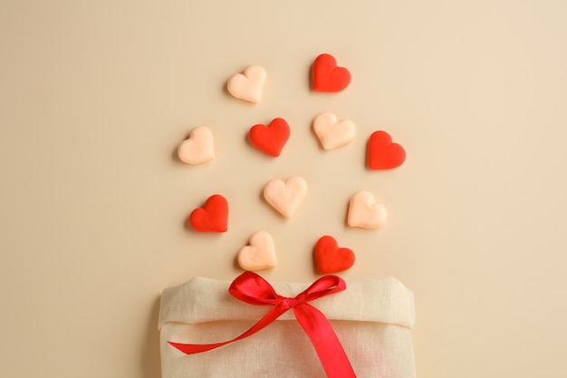 Bag with a bow of sweets-hearts and a ribbon on a beige background. valentine's day holiday. greeting card. stock photo