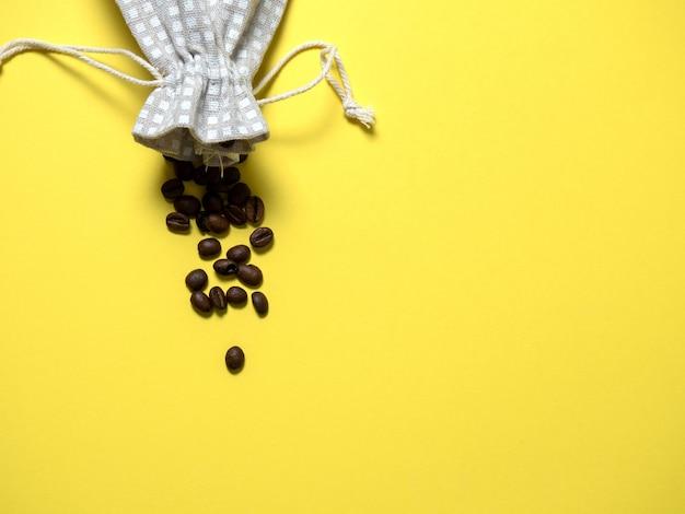 黄色の背景にコーヒー豆が入ったバッグ。フラットレイ、上面図、コピースペース