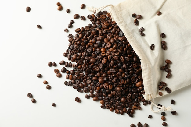Bag with coffee seeds on white