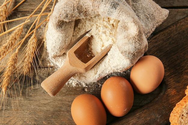 木製のテーブルに小麦粉と卵を入れた袋