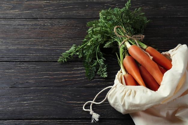 Сумка со свежей морковью на деревянных фоне
