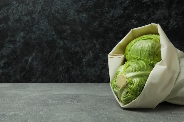 회색 테이블에 신선한 녹색 양배추와 가방
