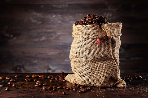 나무 벽 앞에 서있는 신선한 볶은 커피 가방