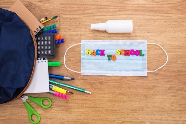 木製のテーブルのフェイスマスクにカラフルな文字で書かれた学用品と学校に戻るバッグ