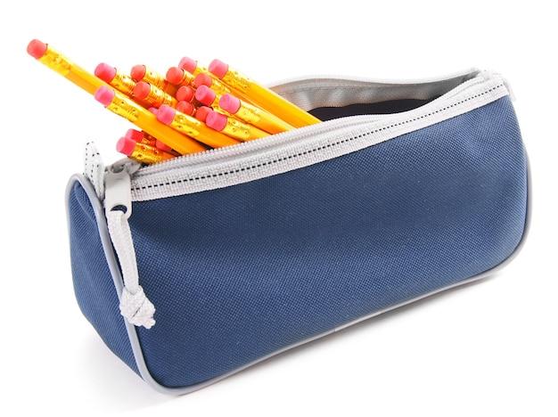 白い背景の上の学校の道具が入ったバッグ。