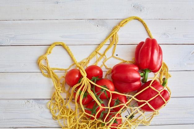 テキストの場所と木製の背景にトマトとピーマンのバッグ。