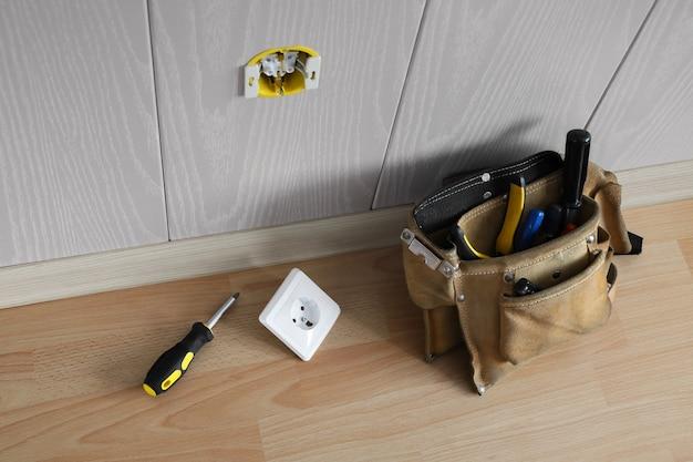 벽에 전기 소켓을 설치하기위한 바닥에 도구와 드라이버가있는 가방