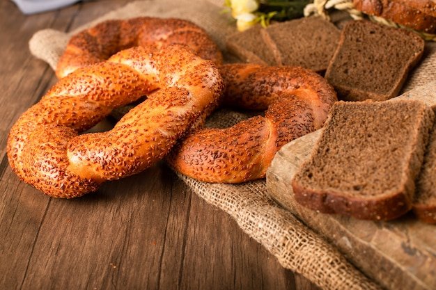 ベーグルとテーブルクロスに暗いパンのスライス