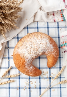 Bagel crescent sprinkled with powdered sugar. on a white blue striped tablecloth. near grain and ears of millet. view from above. country style.