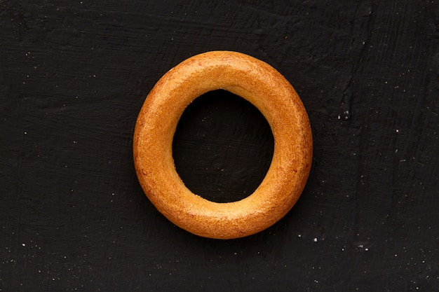Bagel on the dark wooden table, top view
