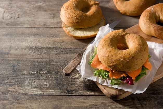 Bagel sandwich with cream cheese, smoked salmon and vegetables on wooden table, copy space