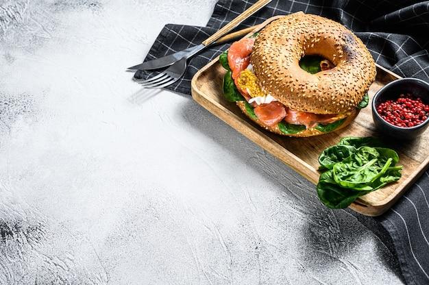 Бублик бутерброд с лососем, сливочным сыром, шпинатом и яйцом на деревянной тарелке. серая поверхность. вид сверху. копировать пространство