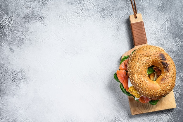 Bagel sandwich with salmon, cream cheese, spinach and egg. gray background
