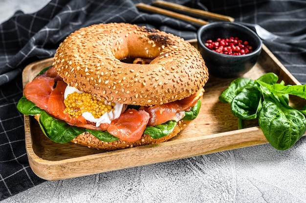 Bagel sandwich with salmon, cream cheese, spinach and egg on a wooden plate. gray surface. top view