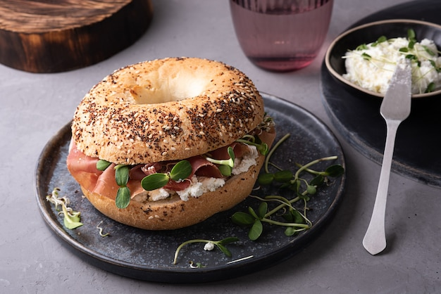 Бублик со сливочным сыром, сухой вяленой ветчиной и микрозеленью на тарелке на сером фоне, бутерброд для завтрака.