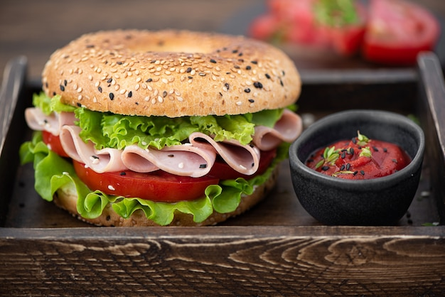 Bagel with ham, lettuce, tomato and tomato sauce